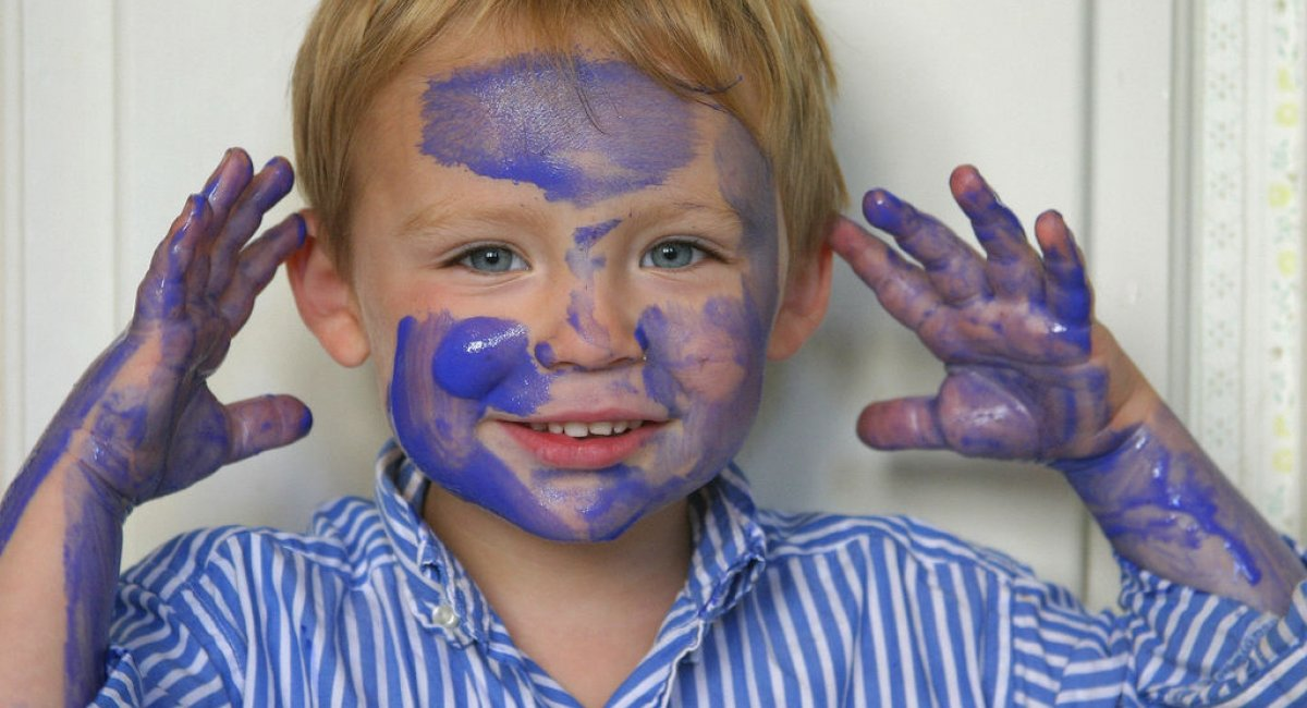 A picture of a little boy with paint on his face.