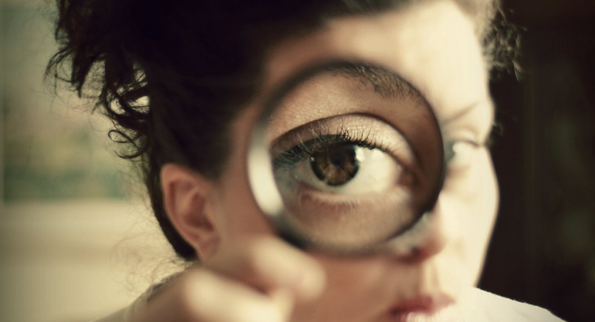 A woman looking through a magnifying glass