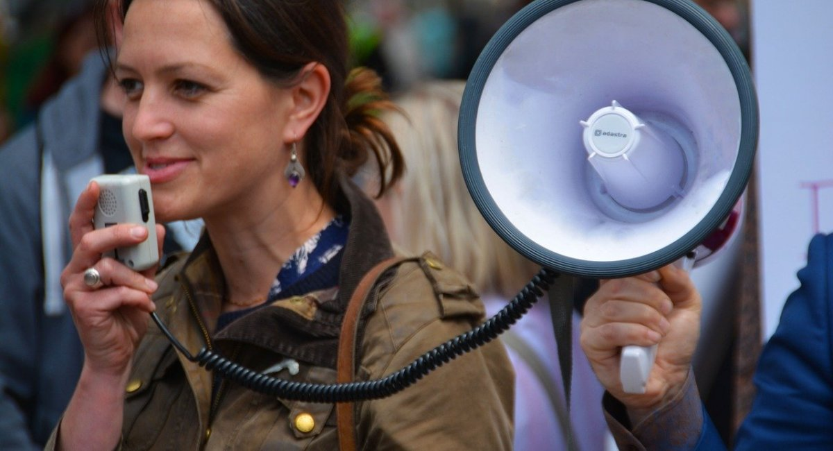 Young woman speaking with a megaphone at a rally