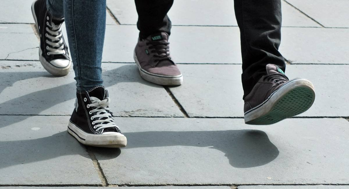 The feet of two people walking together, wearing sneakers