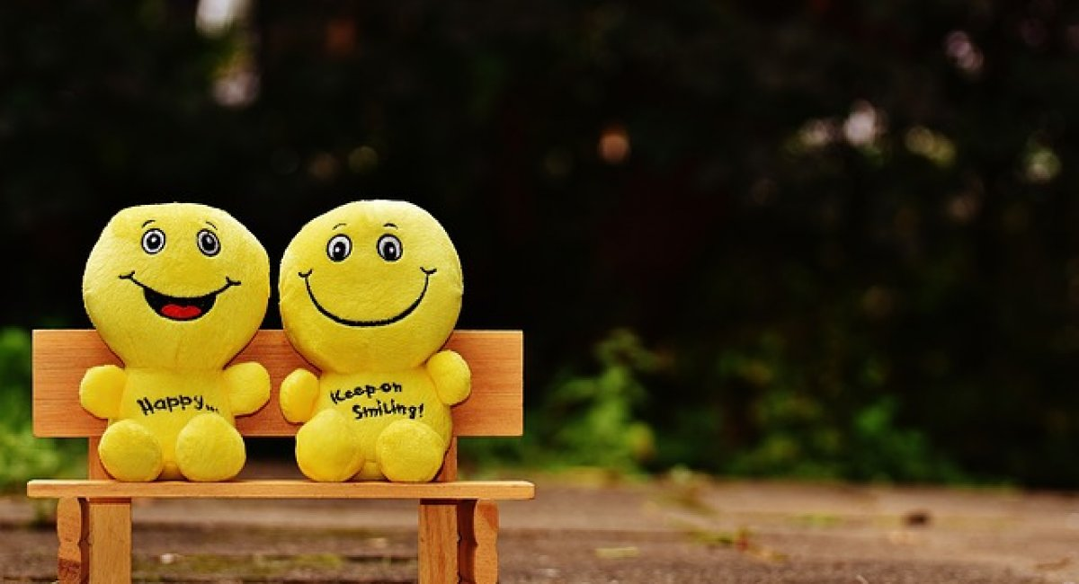 Two Smilies sitting on a bench